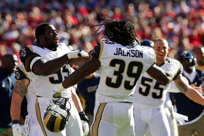 S-Jax celebrates with teammates after his first quarter touchdown run (AP Photo).